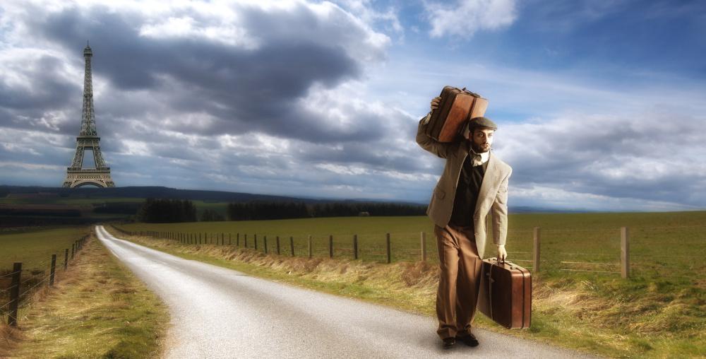 mezczyzna idacy piechota z walizka od strony paryza