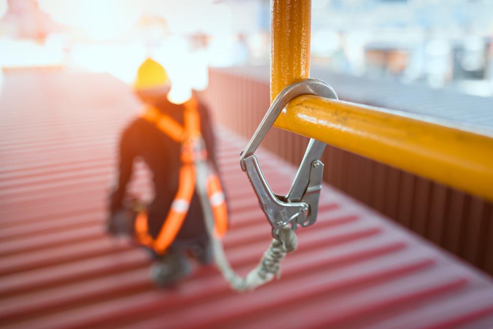 pracownik przypięty do metalowej rury wykonujący prace na dachu